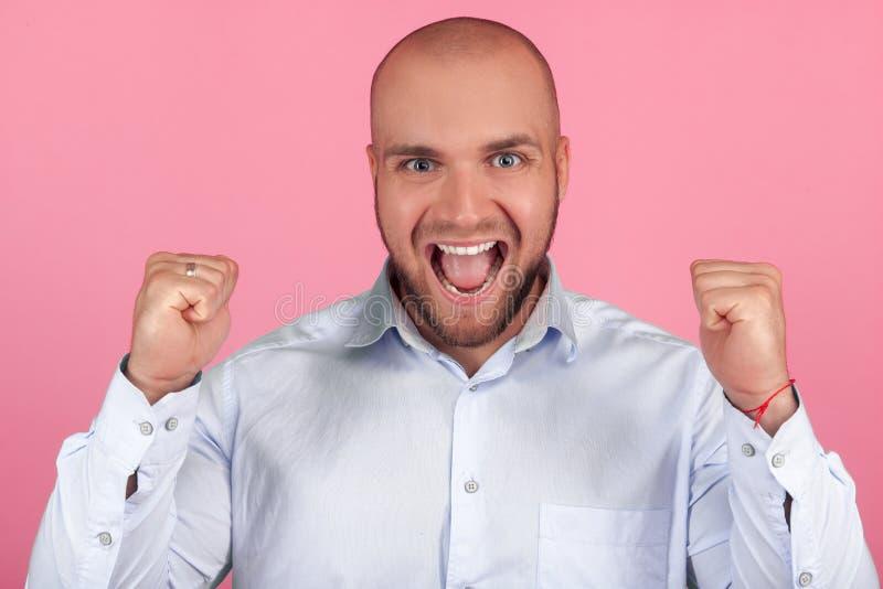 St?enden av den positiva optimistiska skalliga mannen firar hans framg?ng, tagn?var, skrin med lycka, st?r inomhus mot royaltyfria foton