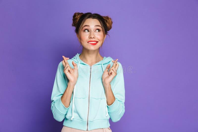 Ståenden av den roliga unga flickan med två bullar som håller fingrar, korsar royaltyfri fotografi
