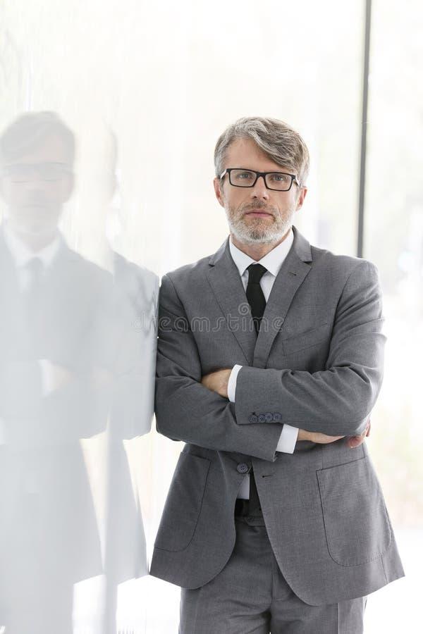 Ståenden av den säkra mogna affärsmannen med armar korsade att luta på väggen på kontoret fotografering för bildbyråer