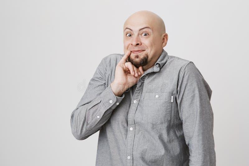 Ståenden av den skalliga skäggiga mannen med det roliga uttryckt som rymmer hans lillfinger nära, skvallrar över vit bakgrund Gra arkivfoton