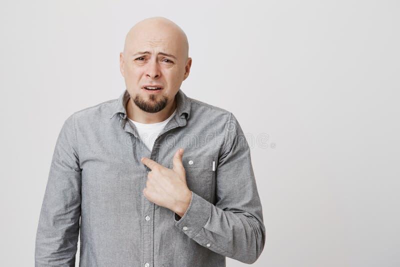 Ståenden av den skalliga stiliga mannen med förvirrat och ifrågasatt uttryck som pekar på hans vuxna man för bröstkorgen gör inte arkivbild