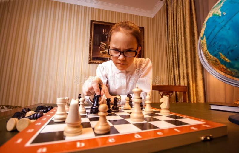 Ståenden av den smarta flickan gör flyttning på schackbräde royaltyfri foto