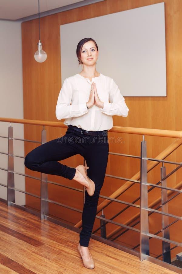 Ståenden av den sportiga unga vita Caucasian affärskvinnan för den slanka passformen som mediterar göra yoga, övar fotografering för bildbyråer