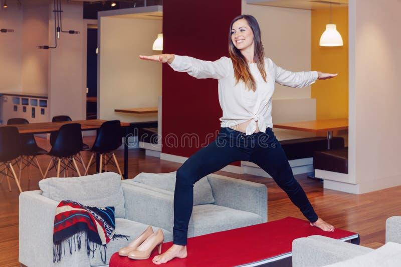 Ståenden av den sportiga unga vita Caucasian affärskvinnan för den slanka passformen som mediterar göra yoga, övar royaltyfri fotografi