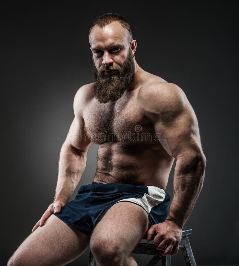 Ståenden av den starka skäggiga mannen med perfekt abs, pecs knuffar, arkivfoto