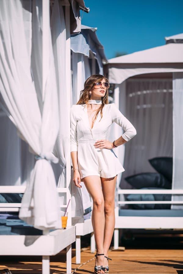 Ståenden av den stilfulla emotionella flickan bär den moderiktiga sommarklänningen som poserar bredvid den exotiska sommarstrande royaltyfria bilder