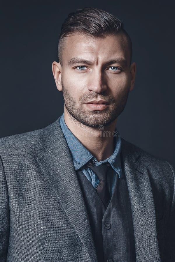 Ståenden av den stilfulla lyckade brutala mannen i grå färger passar med trendig frisyr på bakgrund av den gråa väggen royaltyfria foton