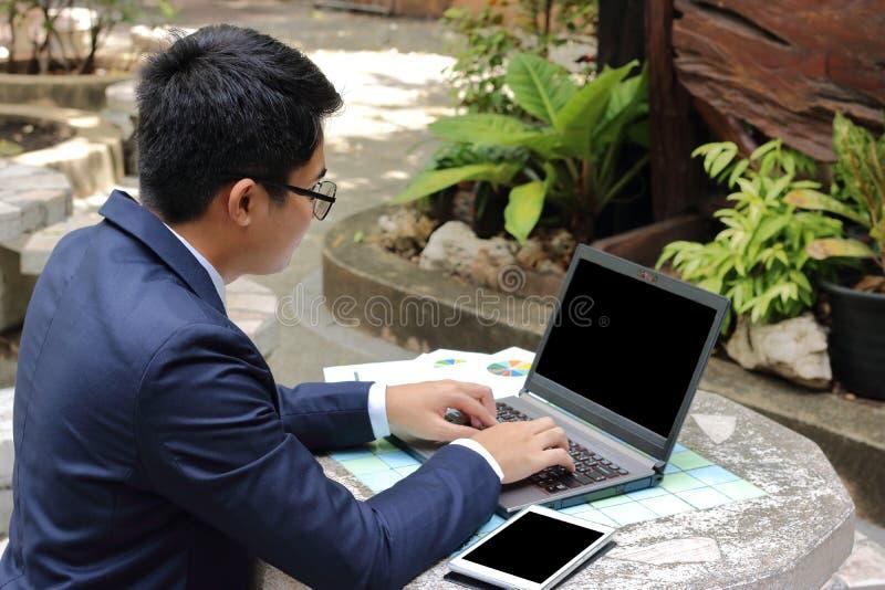 Ståenden av den stiliga affärsmannen som arbetar med bärbar datordatoren i stad, parkerar utomhus arkivbild