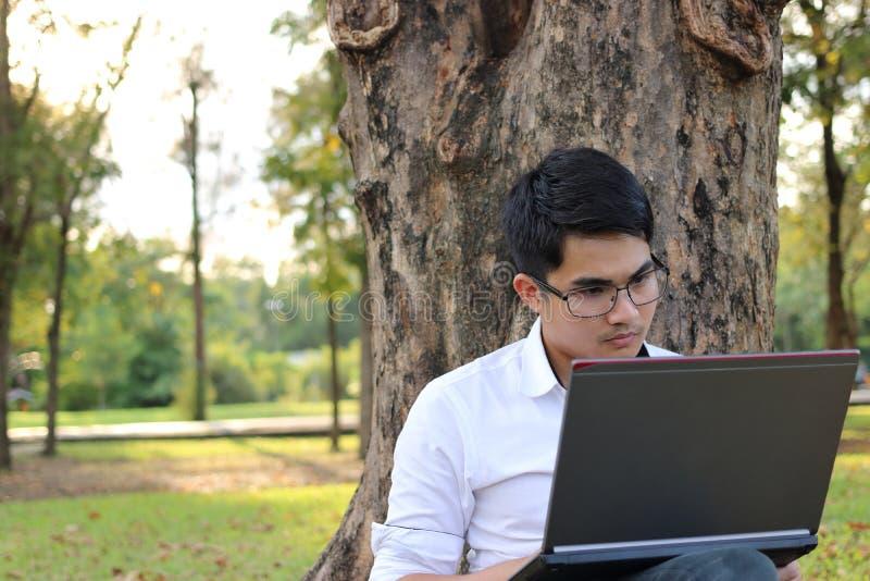 Ståenden av den stiliga asiatiska unga mannen som arbetar på bärbar datordatoren i stad, parkerar royaltyfria bilder