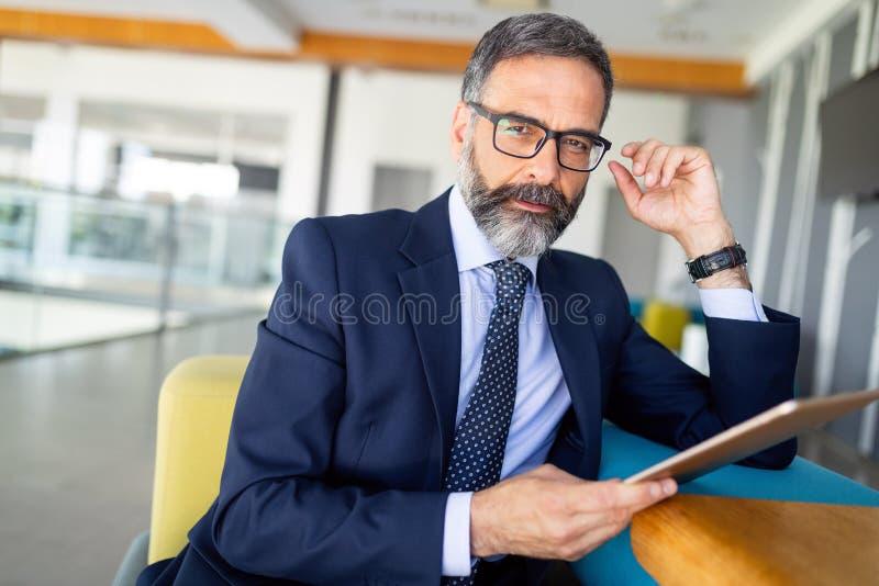Ståenden av den stiliga höga affärsmannen med den digitala minnestavlan i modren kontoret royaltyfri fotografi