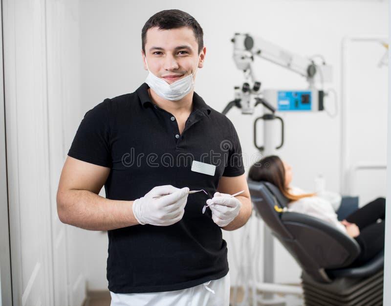 Ståenden av den stiliga manliga tandläkaren som rymmer tand- hjälpmedel - sondera och avspegla på det tand- kontoret dentistry royaltyfri bild