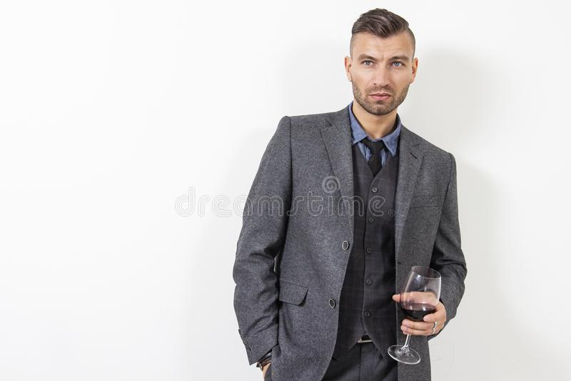 Ståenden av den stiliga mannen i affärsdräkt rymmer exponeringsglas med rött vin på vit bakgrund brutal man royaltyfri foto