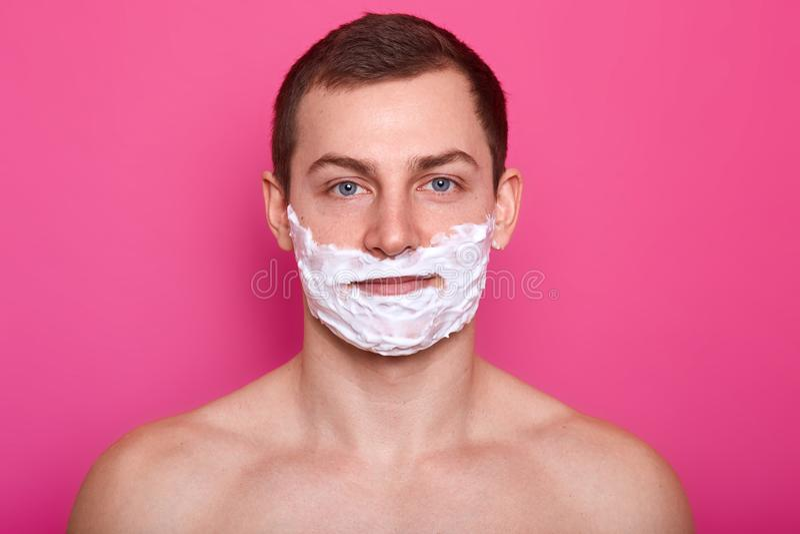 Ståenden av den stiliga mannen med skum på framsida över rosa bakgrund, ser lugna, har angenämt ansiktsuttryck, ser arkivbild