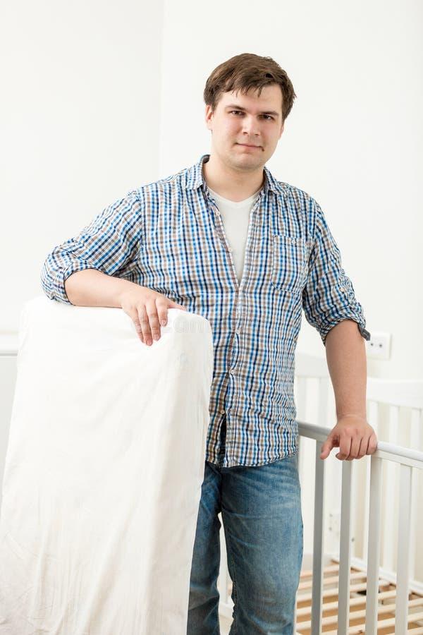 Ståenden av den stiliga mannen som poserar på, behandla som ett barn kåtan för ` s med den nya madrassen arkivbilder