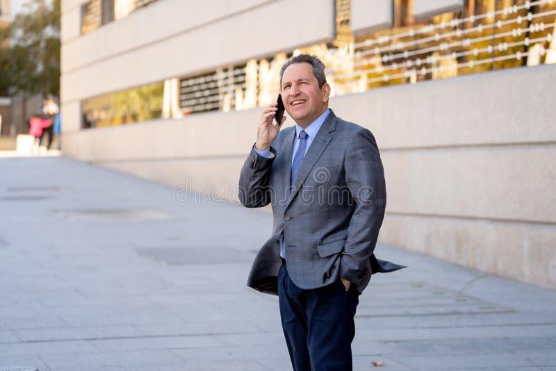 Ståenden av den stiliga mitt åldrades den smarta affärsmannen som går i staden som talar på mobiltelefonen arkivbilder