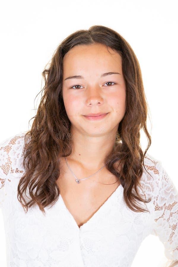 Ståenden av den tonåriga unga kvinnan för den gladlynta nätta brunetten med långt krabbt hår bär t-skjortan som isoleras över vit royaltyfria foton