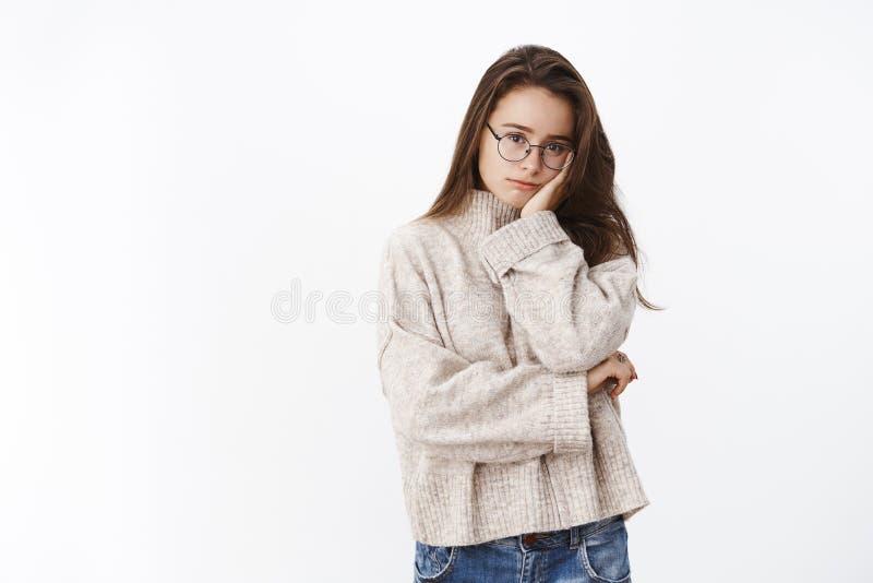 Ståenden av den trötta och tömda gulliga kvinnliga freelanceren i tröja- och PCexponeringsglas som lutar huvudet gömma i handflat royaltyfria bilder