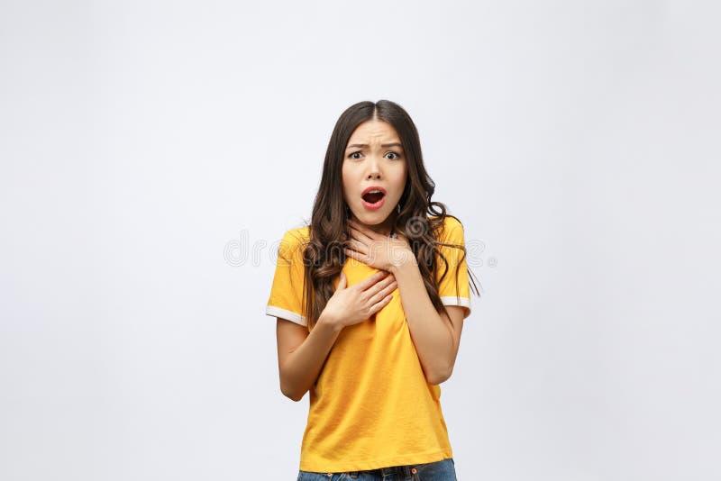 Ståenden av den trevliga chockade positiva gulliga unga flickan i tillfällig gul skjorta, öppnade munnen som isolerades över vit  royaltyfria foton