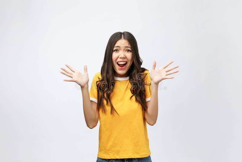 Ståenden av den trevliga chockade positiva gulliga unga flickan i tillfällig gul skjorta, öppnade munnen som isolerades över vit  royaltyfri fotografi