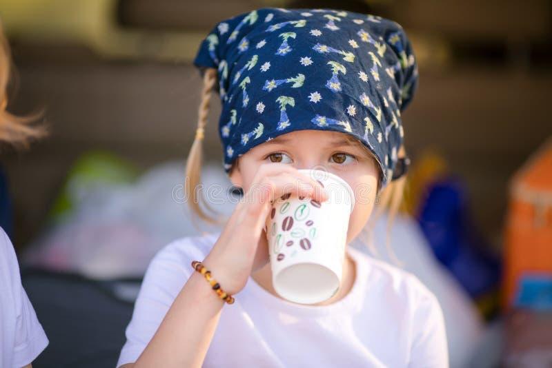 Ståenden av den undrade blonda flickan med två flätade trådar som dricker hennes te royaltyfria foton
