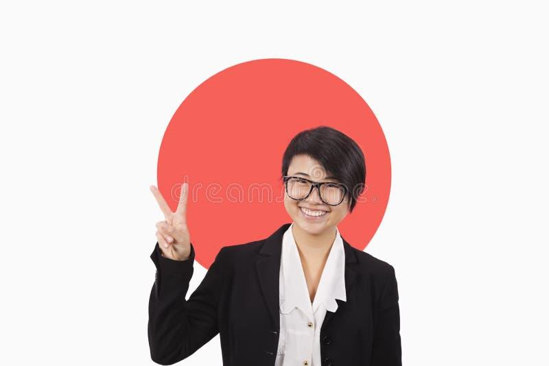 Ståenden av den unga affärskvinnan som gör en gest fred, undertecknar över den japanska flaggan royaltyfri bild