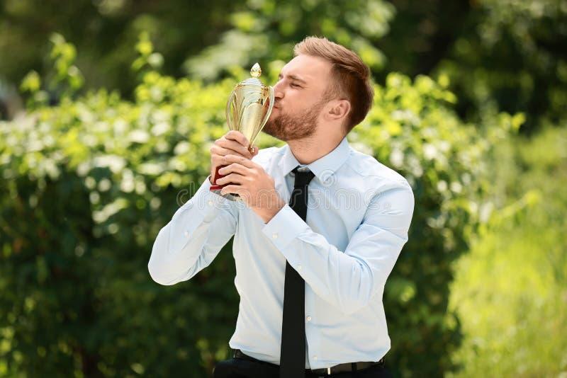 Ståenden av den unga affärsmannen som kysser den guld- trofékoppen parkerar in royaltyfri bild