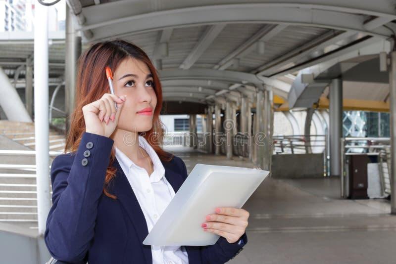 Ståenden av den unga asiatiska affärskvinnan har en bra idé på utomhus- allmänhet Tänkande idéaffärsidé arkivbild