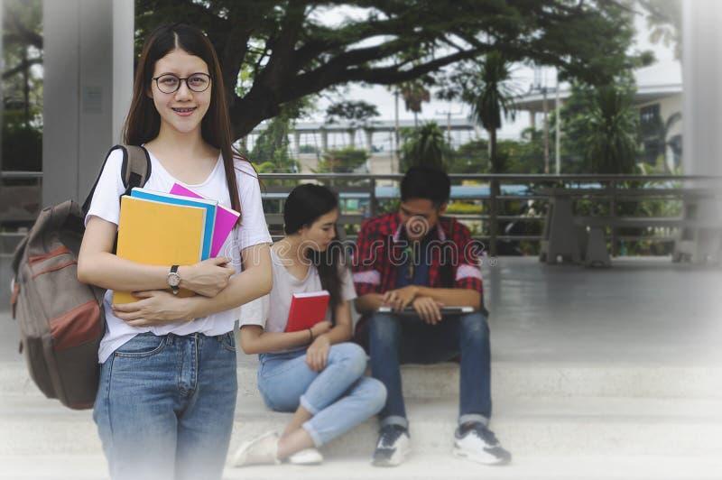 Ståenden av den unga asiatiska kvinnastudenten och vänner handleder e royaltyfri foto