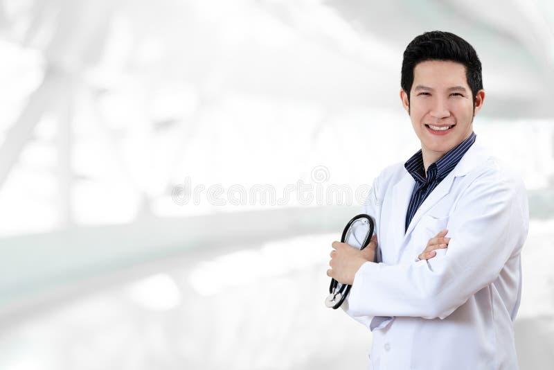 Ståenden av den unga attraktiva asiatiska doktors- eller läkaremannen korsade utrustning för stetoskopet för arminnehavet medicin royaltyfria foton