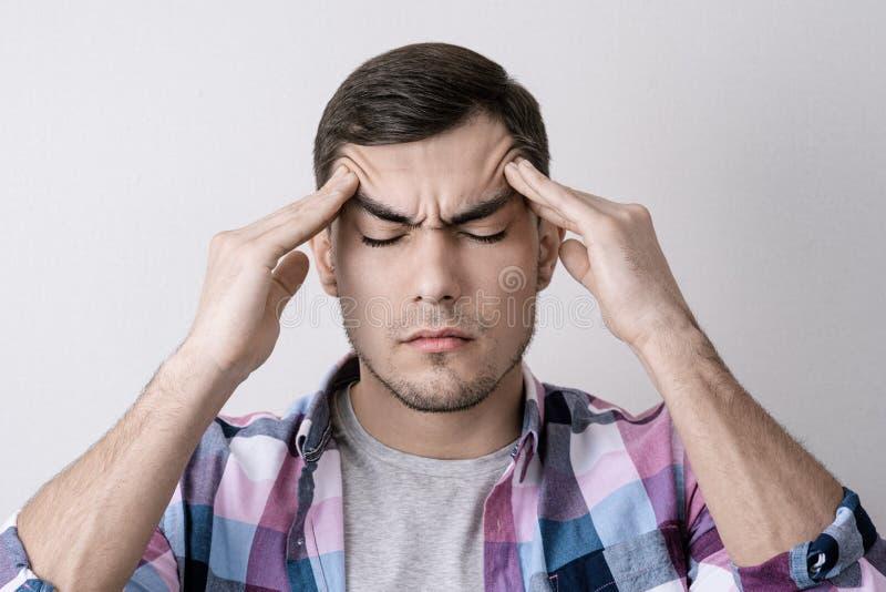 Ståenden av den unga caucasian mannen med huvudvärk som trycker på hans fingrar på hans huvud med hans ögon, stängde sig royaltyfri foto