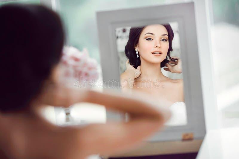 Ståenden av den unga härliga bruden ser henne i spegeln royaltyfri fotografi