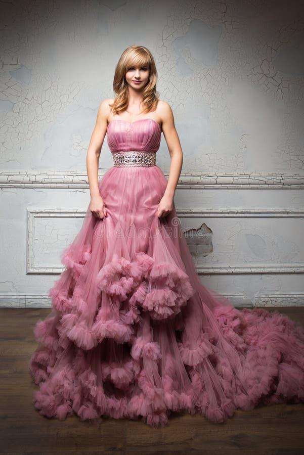 Ståenden av den unga härliga flickan i långa rosa färger klär arkivfoton