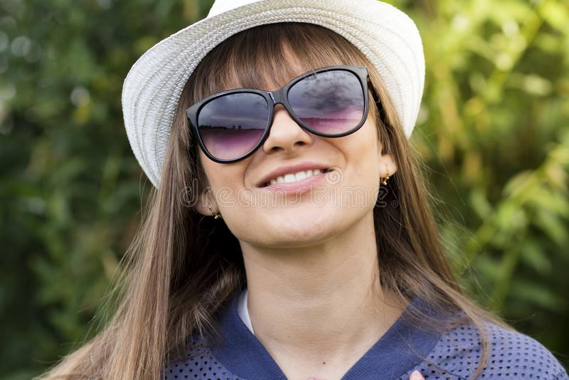 Ståenden av den unga härliga flickan i solglasögon och hatten i bra lynne som ler mot grön sommar, parkerar arkivfoton