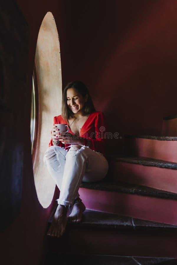 Ståenden av den unga härliga kvinnan som sitter vid fönstret, kopplade av hemma att rymma en kopp te av kaffe Livsstil inomhus arkivfoto