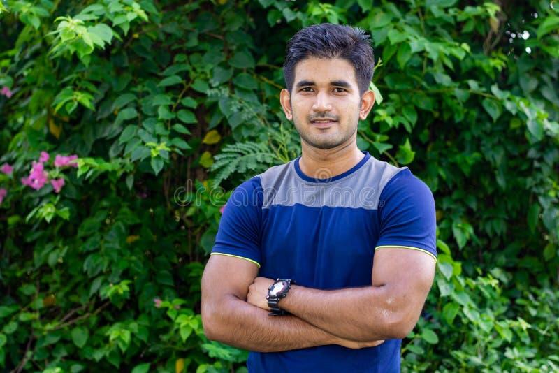 Ståenden av den unga indiska mannen i parkerar på grön bakgrund arkivbild