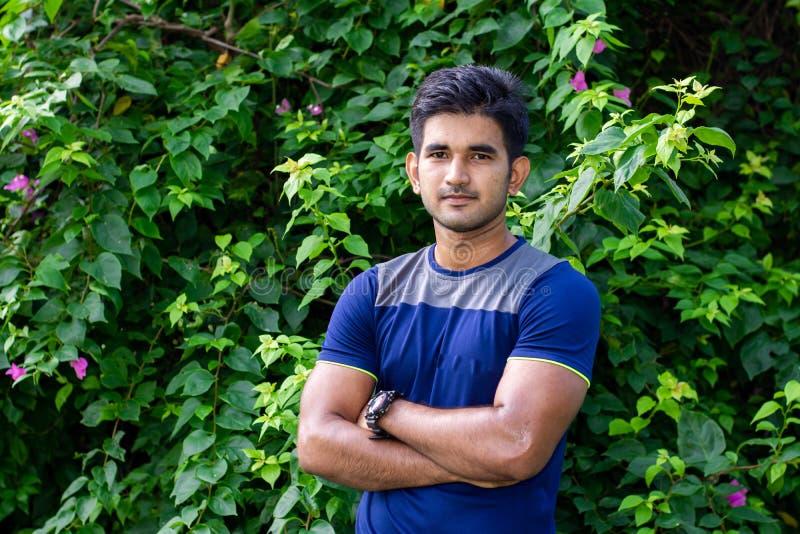 Ståenden av den unga indiska mannen i parkerar på grön bakgrund royaltyfria foton