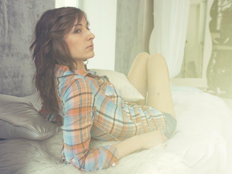 Ståenden av den unga kvinnan i den säng klädde tillfälliga skjortan, solljus, tonade, värme färger arkivbild