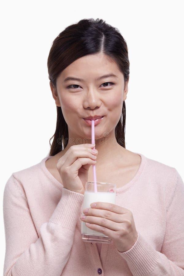 Ståenden av den unga kvinnan i rosa färger som ler och dricker ett exponeringsglas av, mjölkar till och med ett sugrör, studioskot royaltyfri foto