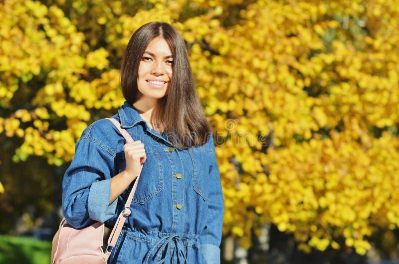 Ståenden av den unga kvinnan med den rosa handväskan i stad parkerar med gula guld- sidor arkivfoton