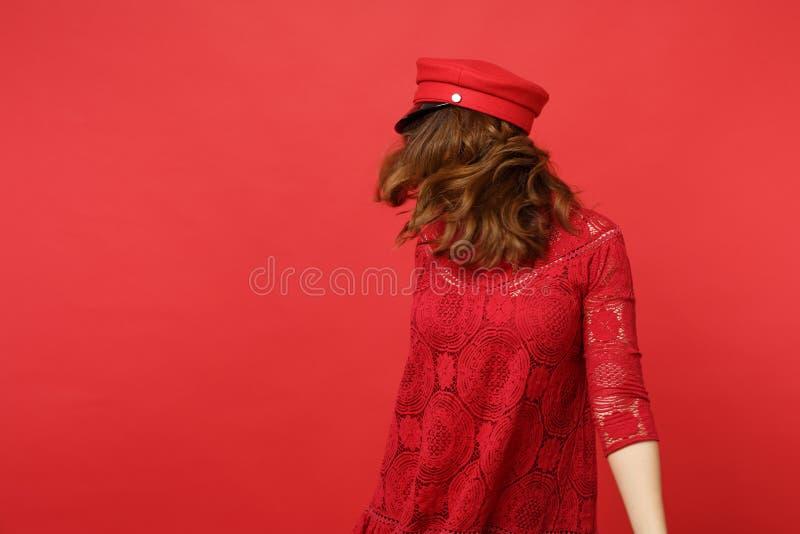 Ståenden av den unga kvinnan snör åt in klänning- och lockanseendet som hoppar med att fladdra hår som isoleras på den ljusa röda royaltyfria bilder
