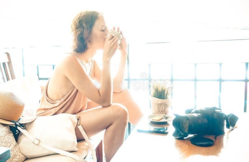 Ståenden av den unga kvinnan som dricker cappuccino kopplar av på, loppögonblick arkivbilder