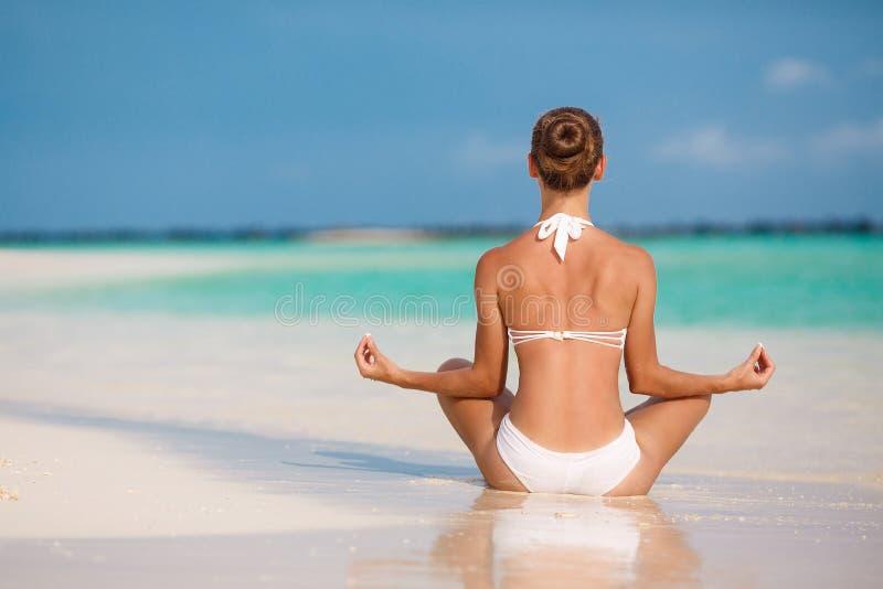 Ståenden av den unga kvinnan som gör yoga, övar på den tropiska maldivian stranden nära havet royaltyfria bilder