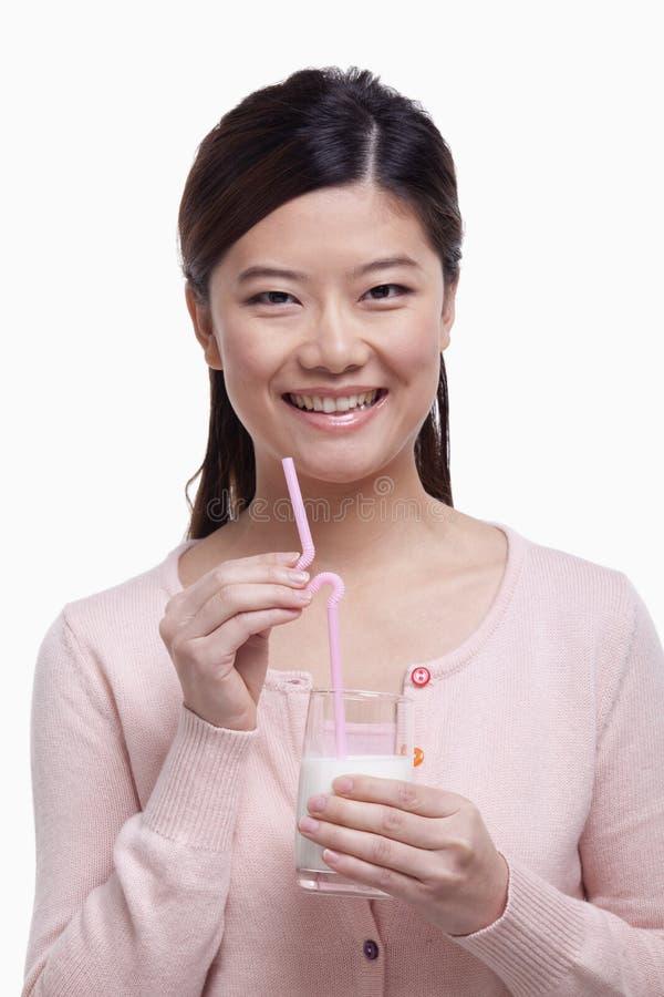 Ståenden av den unga kvinnan som ler och dricker ett exponeringsglas av, mjölkar arkivfoton