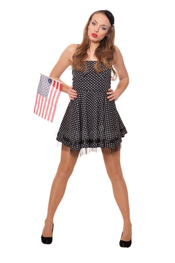Ståenden av den unga kvinnan som poserar med flaggan av USA, isolerade royaltyfri fotografi