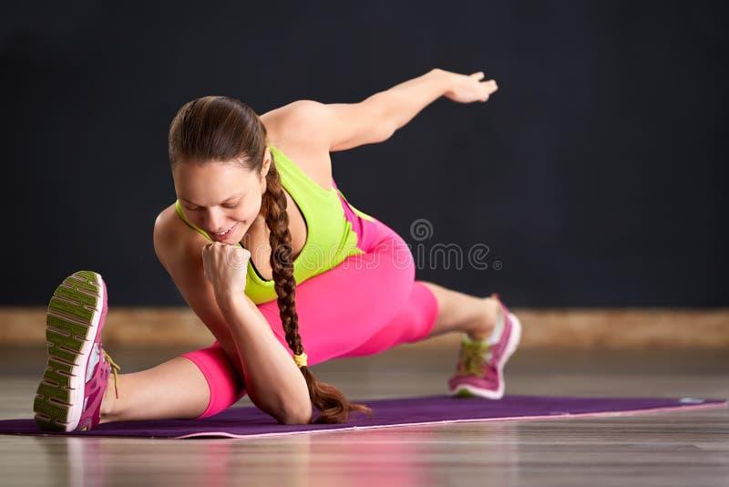 Ståenden av den unga kvinnan som utarbetar på den violetta de matta, övningsyogan och pilatesna, övar och att göra delar royaltyfria foton