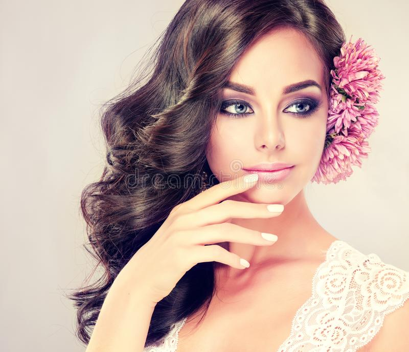 Ståenden av den unga lockiga haired brunetten med livlig östlig stil utgör Eleganta lockiga frisyrer arkivfoto