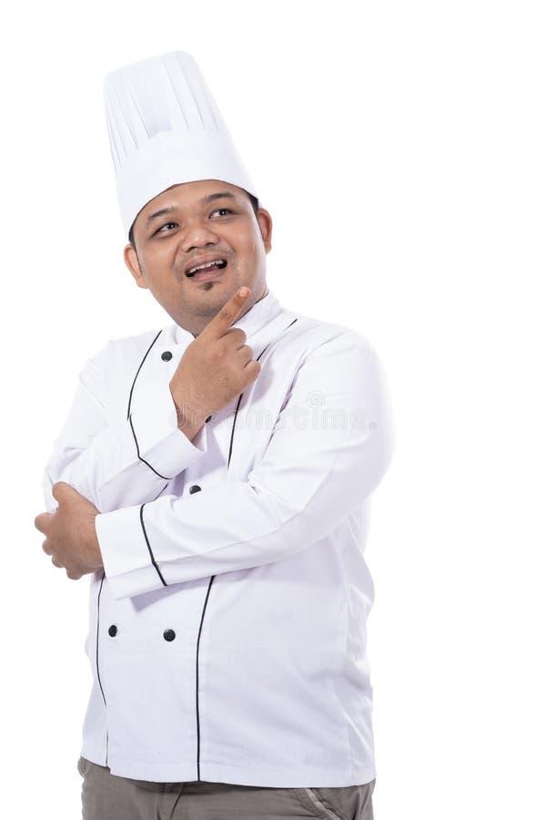 Ståenden av den unga manliga kocken som står säker, poserar blick på en framdel av kameran fotografering för bildbyråer