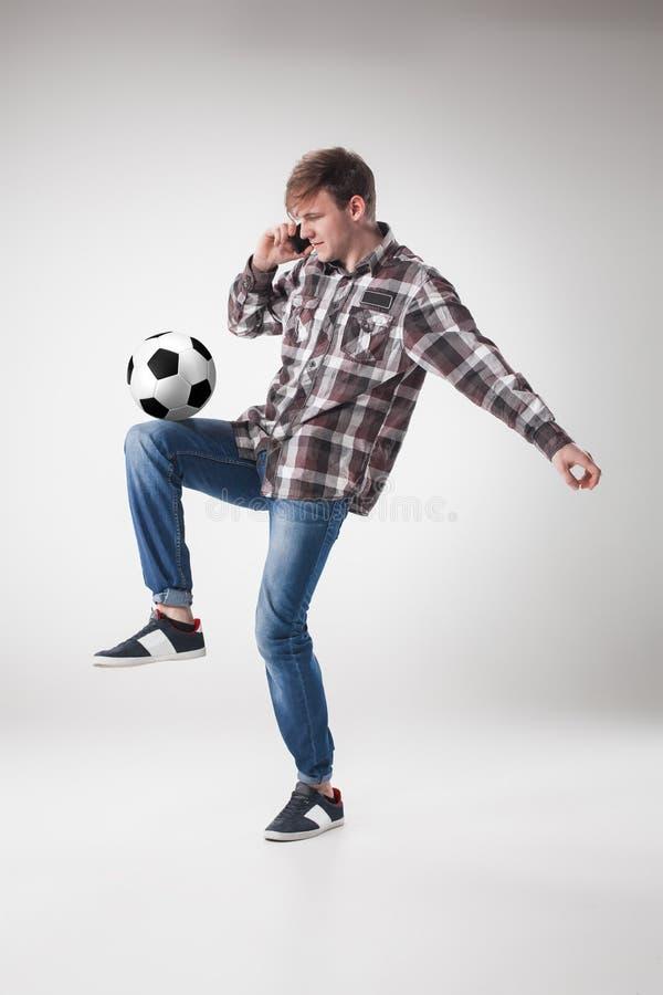 Ståenden av den unga mannen med den smarta telefonen och fotboll klumpa ihop sig arkivfoton