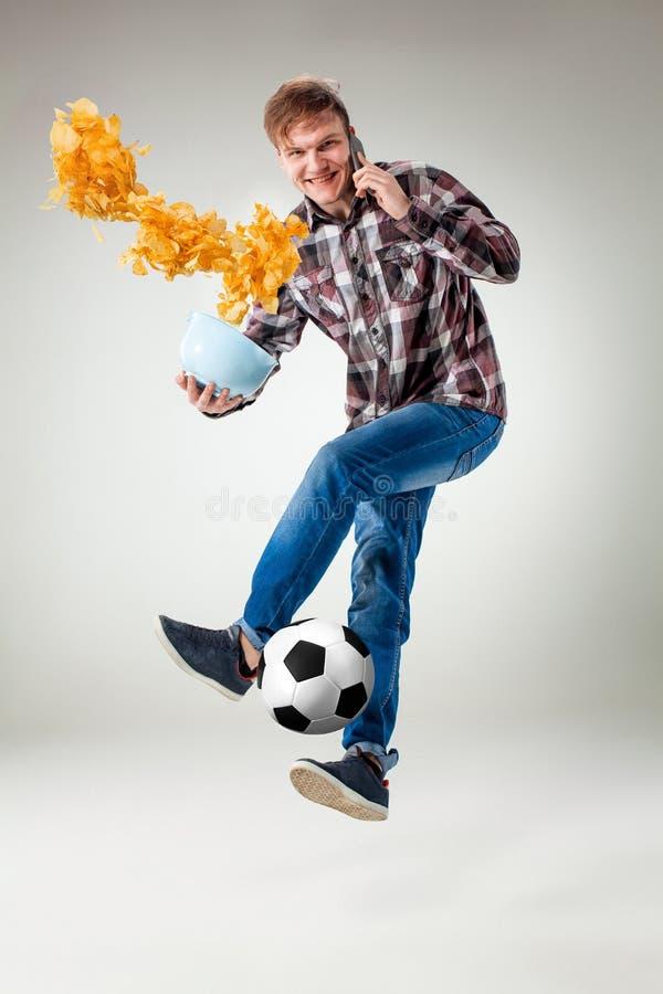 Ståenden av den unga mannen med den smarta telefonen och fotboll klumpa ihop sig royaltyfri bild
