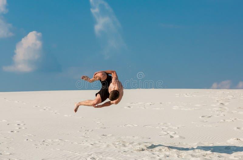 Ståenden av den unga parkourmannen som gör flip eller, slår en kullerbytta på sanden royaltyfri foto
